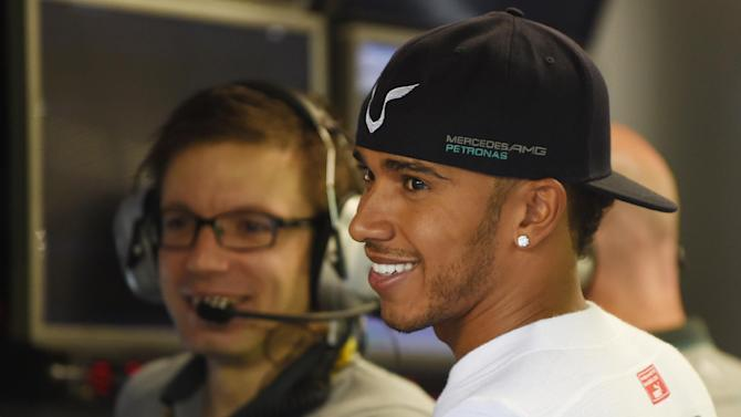 Mercedes driver Lewis Hamilton of Britain (R) chats with his team officers before the first practice session of the Singapore Grand Prix at the Marina Bay Street circuit on September 19, 2014