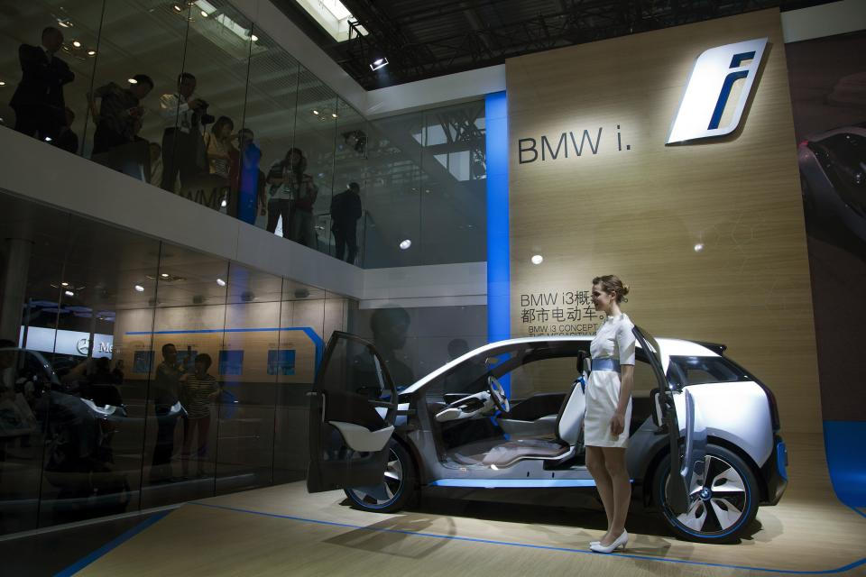 Visitors look at a model standing next to a BMW i3 Concept car on display at the Beijing International Automotive Exhibition in Beijing, China Monday, April 23, 2012. (AP Photo/Andy Wong)