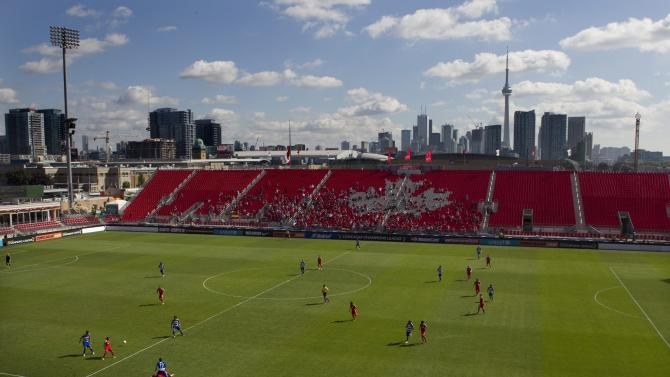 A scattering of fans watch the first half of a CONCACAF Champions League soccer game between Toronto FC and  FC Dallas in Toronto on Thursday, Aug. 25, 2011. The game was replayed after being abandoned because of thunderstorms the night before. (AP Photo/The Canadian Press, Chris Young)