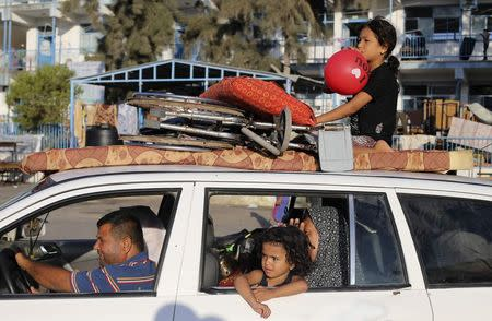 A Palestinian family leaves a United Nations-run school sheltering displaced Palestinians, as they make their way home after a ceasefire was declared, in Khan Younis in Gaza Strip