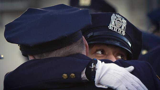 Police officers hug before NYPD officer Rafael Ramos' funeral at Christ Tabernacle Church in the Queens borough of New York