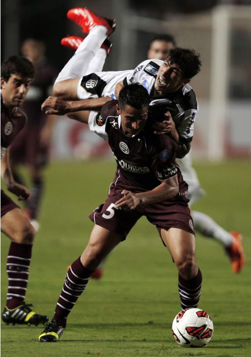 Rildo of Brazil's Ponte Preta falls over Gonzalez of Argentina's Lanus during their Copa Sudamericana first leg final soccer match in Sao Paulo