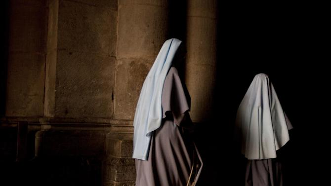 Nuns walk during the Sunday Easter mass at the Church of the Holy Sepulcher, traditionally believed to be the site of the crucifixion of Christ, in Jerusalem's Old City, Sunday, March 31, 2013. (AP Photo/Sebastian Scheiner)