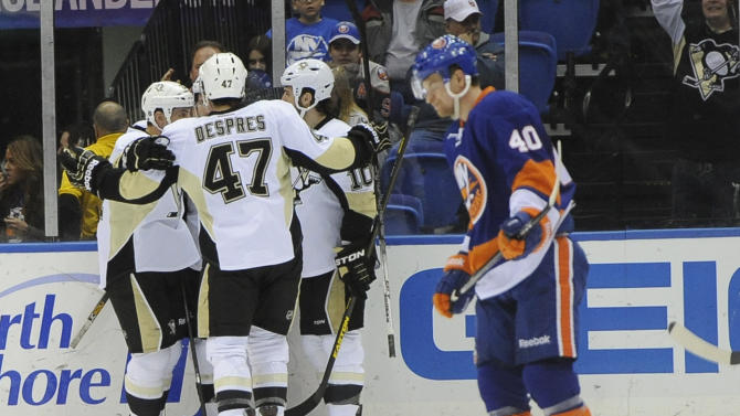Pittsburgh Penguins' Craig Adams (27),  Simon Despres (47) and Tanner Glass (10) celebrate Joe Vitale's goal as New York Islanders' Michael Grabner (40) skates away in the second period of an NHL hockey game on Friday, March 22, 2013 at Nassau Coliseum  in Uniondale, N.Y. (AP Photo/Kathy Kmonicek)