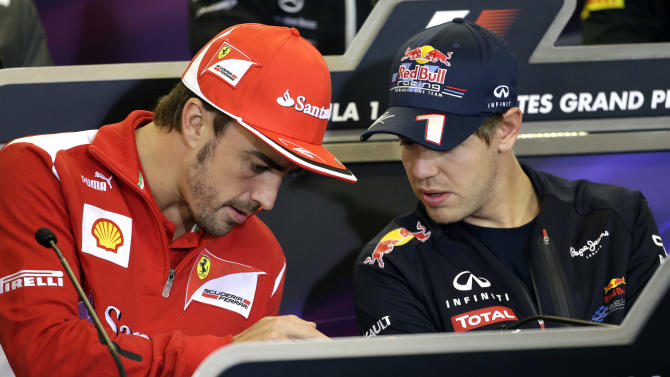 Red Bull driver Sebastian Vettel, right, of Germany, looks at the smartphone of Ferrari driver Fernando Alonso, left, of Spain, during a news conference at the Circuit of the Americas race track Thursday, Nov. 15, 2012, in Austin, Texas. Formula One's U.S. Grand Prix auto race is scheduled for Sunday at the track. (AP Photo/David J. Phillip)