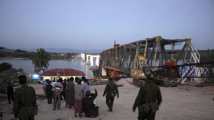 Local residence look at  the bridge damaged by a strong earthquake as Myanmar soldiers walk past them, in Kyaukmyaung township, Shwebo, Sagaing Division, northwest of Mandalay, Myanmar, Sunday, Nov.11, 2012. A strong earthquake of magnitude-6.8 struck northern Myanmar on Sunday, collapsing a bridge and a gold mine, damaging several old Buddhist pagodas and leaving as many as 12 people feared dead.(AP Photo)
