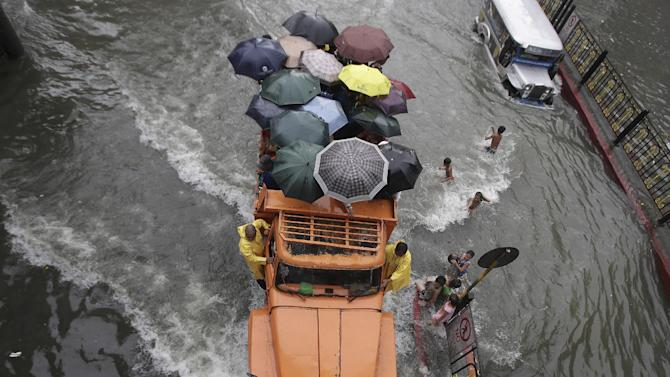 A truckload of stranded commuters cross a flooded street in Manila, Philippines Monday, Aug. 19, 2013. Torrential rains brought the Philippine capital to a standstill Monday, submerging some areas in waist-deep floodwaters and making streets impassable to vehicles while thousands of people across coastal and mountainous northern regions fled to emergency shelters. (AP Photo/Aaron Favila)