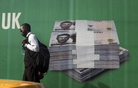 A man walks past a promotional banner showing a photograph of a pile of Nigerian naira along a road in Lagos