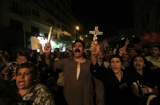 FILE - In this Tuesday, Oct. 4, 2011 file photo, Egyptian Copts hold Christian crosses and chant slogans as they demonstrate against the sectarian violence, in downtown Cairo, Egypt.  In the past few weeks, riots have broken out at two churches in southern Egypt, prompted by Muslim crowds angered by rumors that Christians were building new churches. The violence is particularly frustrating for Christians because soon after Mubarak's fall the new government promised to review and lift heavy restrictions on building or renovating churches that Mubarak's regime had long enforced. The promise raised hopes among Christians that they would be put on equal footing with Muslims and establish a clear legal right to build, resolving an issue that in recent years has increasingly sparked riots. But the review never came, and ultraconservative Muslim clerics have increased their rhetoric against Christians, including accusing them of seeking to spread their faith with new churches.(AP Photo/Khalil Hamra, File)