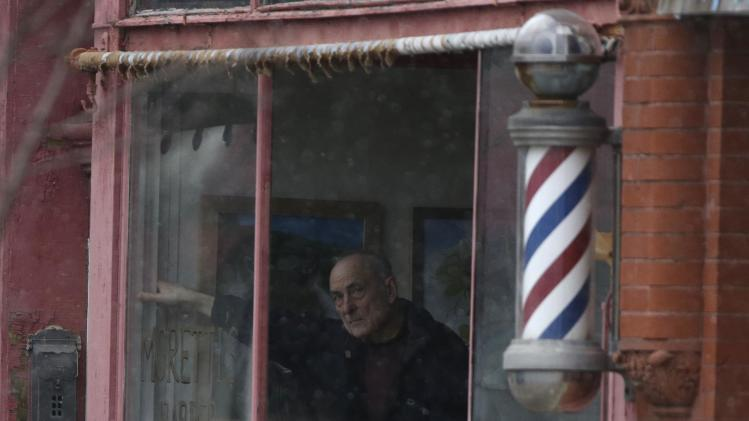 A man watches from the window of a barber shop as officials search down the street for a suspect in two shootings that killed four and injured at least two on, Wednesday, March 13, 2013 in Herkimer, N.Y. A man neighbors said rarely spoke to them started a fire in his apartment on Wednesday, shot four people dead at a couple of businesses in his hometown and a neighboring village and then exchanged gunfire with police officers who surrounded an abandoned building where he apparently was holed up, authorities said. (AP Photo/Mike Groll)
