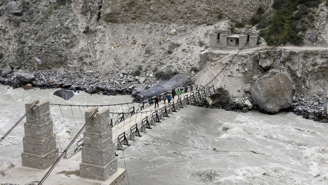 A trekking group walks over a rope bridge across the Braldu River in the Karakoram mountain range near the village of Askole in Pakistan August 27, 2014. (REUTERS/Wolfgang Rattay)