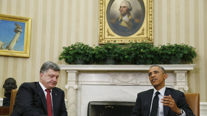 U.S. President Barack Obama talks while Ukraine's President Petro Poroshenko listens, as they address the media during a meeting in the Oval Office of the White House in Washington