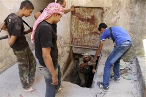 A Free Syrian Army fighter helps a fellow fighter get…