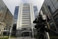 A news camera films the offices of News International company headquarters in London, Saturday, Jan. 28, 2012. British police on Saturday arrested four people, including a police officer, on suspicion of corruption as part of an ongoing investigation into police bribery by the now defunct News of the World tabloid newspaper, and the police said the arrests were made as a result of information provided by Murdoch's News Corp., and officers were searching the east London headquarters of the media mogul's British newspapers for evidence. (AP Photo/Sang Tan)