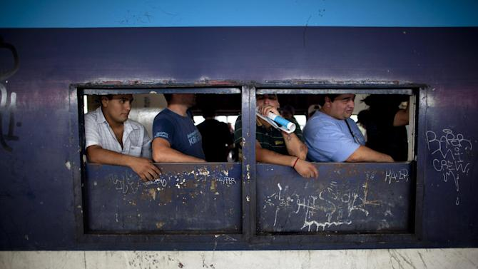 In this Jan. 28, 2013 photo, passengers looks through the windows of a wagon leaving the  Once train station in Buenos Aires, Argentina. Nearly a year after a train crash killed 51 people and injured 800 others on Feb. 22, 2012, exposing systemic corruption and other failures in Argentina's transportation systems, the victims' families and other passengers are as angry as ever over a litany of promised improvements and safety measures that have not been made. (AP Photo/Natacha Pisarenko)