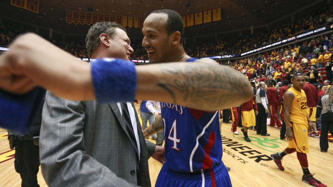 Kansas head coach Bill Self, left, and guard Travis Releford (24) celebrate their 108-96 overtime win against Iowa State in an NCAA college basketball game, Monday, Feb. 25, 2013, in Ames, Iowa. Self earned his 500th career victory with the win. (AP Photo/Justin Hayworth)