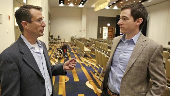 In this May 6, 2013 photo, Michael Goldfarb, left, and Ryan Farris, co-inventors of the Indego wearable robot, speak during a meeting of the American Spinal Injury Association at a downtown hotel in Chicago. Their 27-pound invention snaps together from pieces and fits into a backpack and their goal is for the user to be able to carry it on a wheelchair, put it together, strap it on and walk independently. The device is among several competing products that hold promise for people with spinal injuries, like Gore, and for people with multiple sclerosis and cerebral palsy or for those recovering from strokes. (AP Photo/M. Spencer Green)