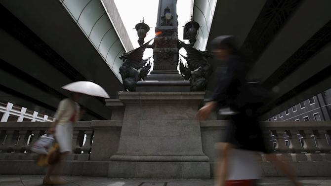 Pedestrians walk in front of a stone statue under a Metropolitan Expressway at a business district in Tokyo