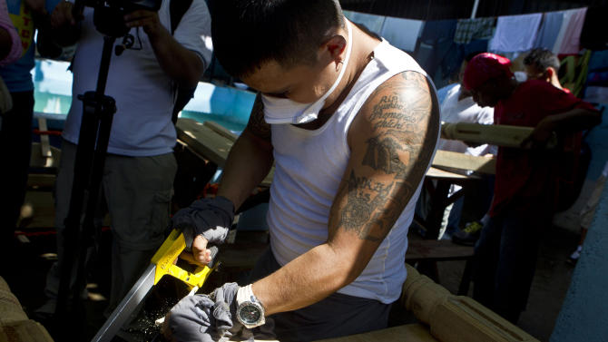 A gang member of the Mara Salvatrucha, MS, cuts wood as he works in a carpentry workshop inside the San Pedro Sula prison in Honduras, Tuesday, May 28, 2013. Honduras' largest and most dangerous street gangs have declared a truce, offering the government peace in exchange for rehabilitation and jobs. A Mara Salvatrucha spokesman says the gang and a rival known as 18th Street will commit to zero violence and zero crime in the streets as first step show of good faith. (AP Photo/Esteban Felix)