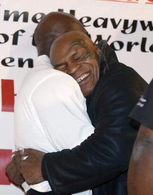Former heavyweight champion Mike Tyson hugs fellow former champion Evander Holyfield during a promotional event for Holyfield's Real Deal barbecue sauce at a Chicago grocery store Saturday, Feb. 16, 2013. (AP Photo/Charlie Arbogast)