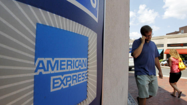 FILE - In this July 19, 2011 file photo, passers-by walk past an American Express logo near the entrance to a bank in the Harvard Square neighborhood of Cambridge, Mass. American Express Co.. reports quarterly financial results on Tuesday, July 29, 2014. (AP Photo/Steven Senne, File)