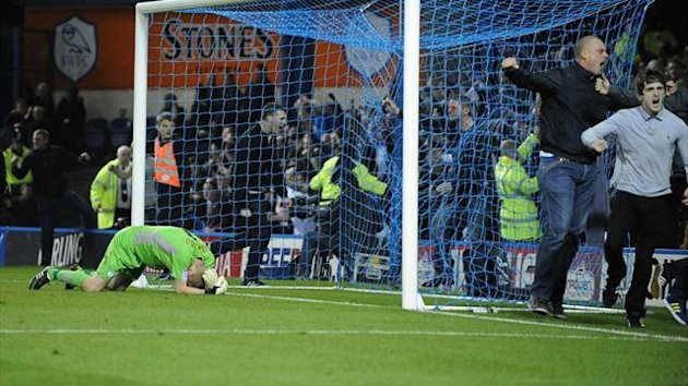 Sheffield Wednesday goalkeeper Chris Kirkland lays on the ground after been struck by a Leeds United fan as other fans run onto the pitch (PA Photos)