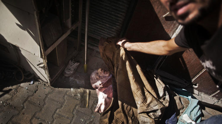 FILE - In this Wednesday, Sept. 19, 2012 file photo, the body of an elderly man, said by rebels to be a Coptic Christian, lies at the door of a hospital controlled by the Free Syrian Army in Aleppo, Syria. Christians, who make up about 10 percent of Syria's population of more than 22 million, say they are particularly vulnerable to the violence that has been sweeping the country since March 2011. They are fearful that Syria will become another Iraq, with Christians caught in the crossfire between rival Islamic groups. (AP Photo/Manu Brabo, File)