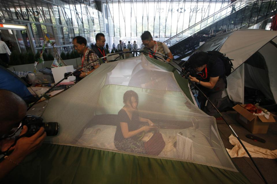 A protester sits inside a tent as bailiffs evict Hong Kong's Occupy activists from a public space underneath HSBC's Asian headquarters Tuesday, Sept. 11, 2012. The protesters had ignored a court order requiring them to leave the site by Aug. 27.  (AP Photo/Kin Cheung)