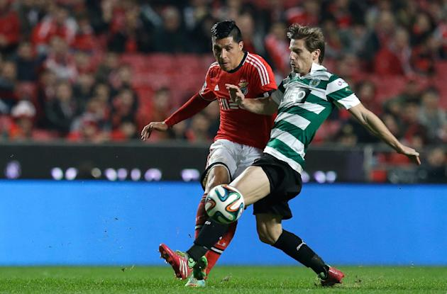 Benfica's Ezequiel Garay, from Argentina, left, fights for the ball with Sporting's Adrien Silva during their Portuguese league soccer match Tuesday, Feb. 11, 2014, at Benfica's Luz stadiu