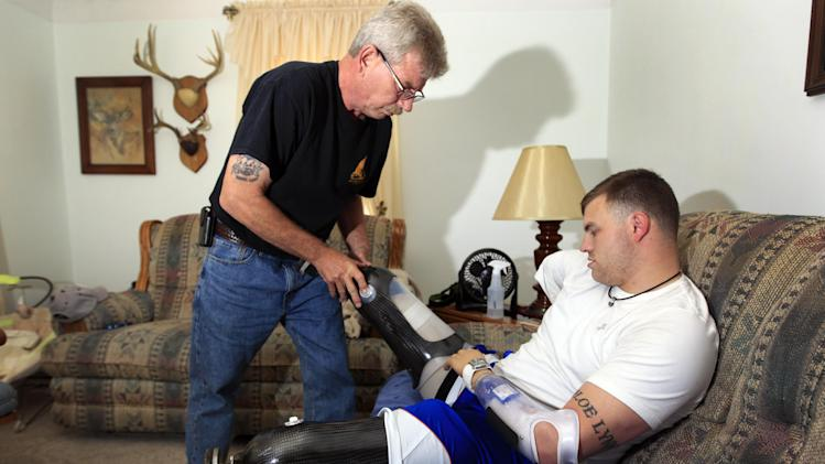 Army Staff Sgt. Travis Mills, right, is helped with his home legs by his father, Dennis Mills at his boyhood home in Vassar, Mich., Thursday, Oct. 4, 2012. Mills is visiting his hometown for the first time since losing all four limbs while fighting in Afghanistan. Mills, his wife, Kelsey, and their 1-year-old daughter, Chloe, will be the grand marshals of Vassar High School's homecoming parade on Thursday evening. (AP Photo/Carlos Osorio)