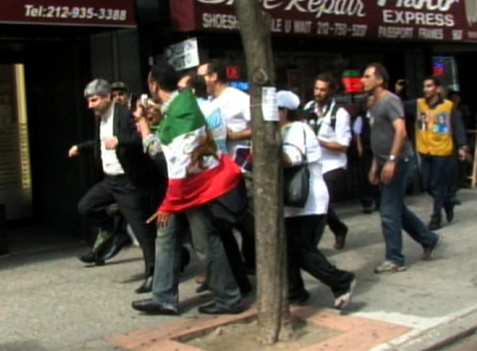 In this image taken from video obtained by AP Television, Iranian Deputy Foreign Ministry spokesman Ramin Mehmanparast, left, stumbles while being followed by a small group of protesters on the street near the United Nations headquarters, Wednesday, Sept. 26, 2012 in New York. (AP Photo/Monica Gutierrez)