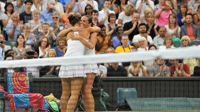 Italy's Sara Errani (L) and Roberta Vinci celebrate on match point winning their women's doubles final match against Hungary's Timea Babos and France's Kristina Mladenovic on day 12 of the 2014 Wimbledon Championships in Wimbledon on July 5, 2014