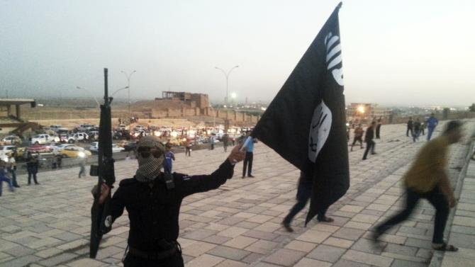 File photo of a fighter of the ISIL holding a flag and a weapon on a street in Mosul