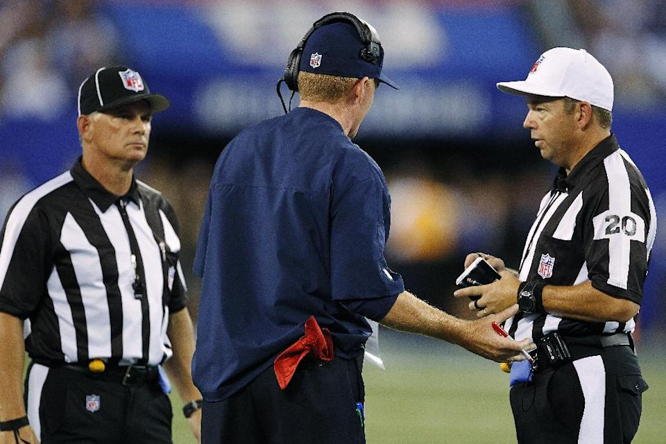 Dallas Cowboys head coach Jason Garrett, center, argues with referee Jim Core (20) during the first half of an NFL football game against the New York Giants, Wednesday, Sept. 5, 2012, in East Rutherford, N.J. (AP Photo/Julio Cortez)