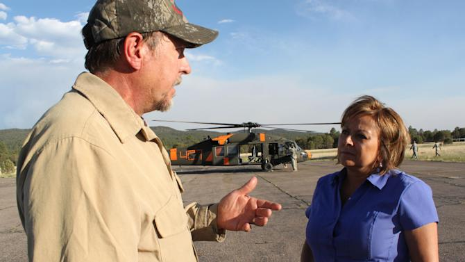 Operations section chief Danny Montoya, left, talks to Gov. Susana Martinez about the behavior of the Whitewater-Baldy fire burning near Reserve, N.M., after an aerial tour on Thursday, May 31, 2012. The fire has burned more than 190,000 acres to become the largest fire in New Mexico's recorded history. (AP Photo/Susan Montoya Bryan)