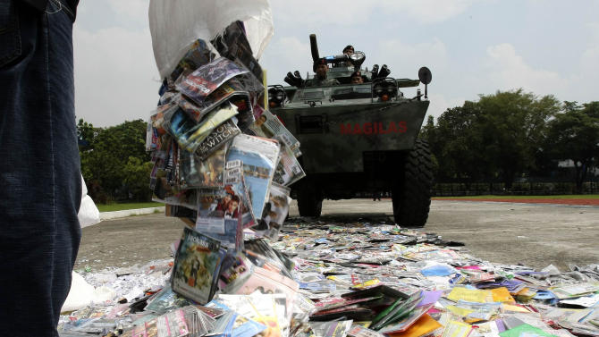A government worker dumps pirated DVDs to be ran over by an armored personnel carrier of the Philippine National Police during ceremonial destruction of counterfeit goods seized in raids recently at parade grounds of the police headquarters at suburban Quezon city, northeast of Manila Thursday June 30, 2011. The ceremonial destruction of pirated DVDs and other counterfeit goods was done to coincide with the global celebration and awareness campaign known as World Anti-Counterfeiting Day. (AP Photo/Bullit Marquez)