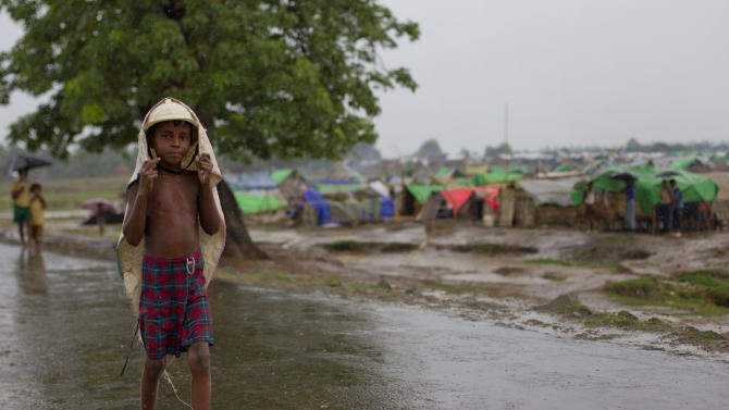 An internally displaced Rohingya boy uses a polyethylene bag to shelter from rain as he walks pass a makeshift camp for Rohingya people in Sittwe, northwestern Rakhine State, Myanmar, Tuesday, May 14, 2013. (AP Photo/Gemunu Amarasinghe)