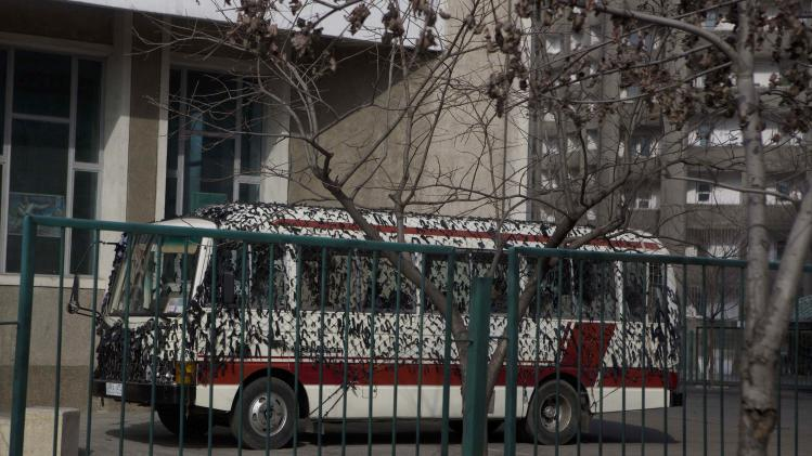 In this Sunday, March 9, 2013 photo, a bus is covered in camouflage netting in parking lot of a building in Pyongyang, North Korea. (AP Photo/David Guttenfelder)