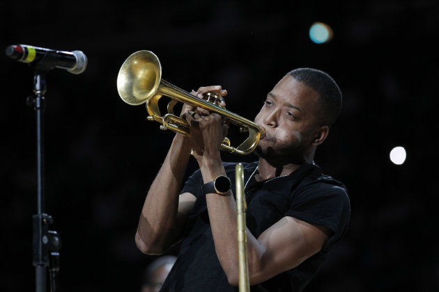 "FILE - This March 14, 2012 file photo shows Troy ""Trombone Shorty"" Andrews performing at the half time of the New Orleans Hornets Los Angles Lakers NBA basketball game in New Orleans. Andrews and actor Gary Sinise will lead the parade of the Krewe of Orpheus on the evening of Lundi Gras, the day before Fat Tuesday. The celebrity riders were announced Thursday, Dec. 6, 2012, at Mardi Gras World, the huge studio where many Carnival floats are built. Orpheus marks its 20th anniversary when it parades Feb. 11. (AP Photo/Bill Haber)"