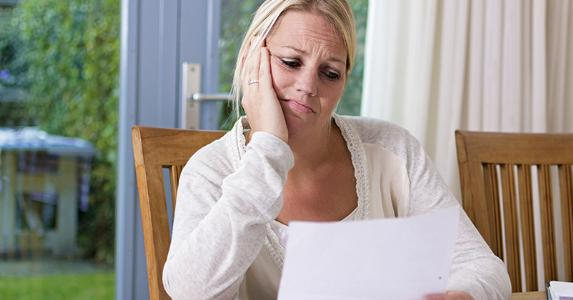 Woman looking sadly at paper copyright Twin Design/Shutterstock.com