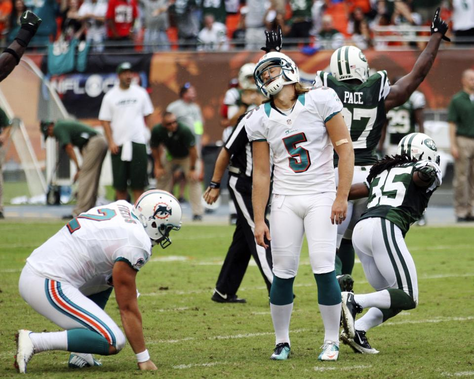 Miami Dolphins kicker Dan Carpenter (5) reacts after missing a field goal during overtime of an NFL football game against the New York Jets, Sunday, Sept. 23, 2012, in Miami. The Jets won 23-20. (AP Photo/Wilfredo Lee)