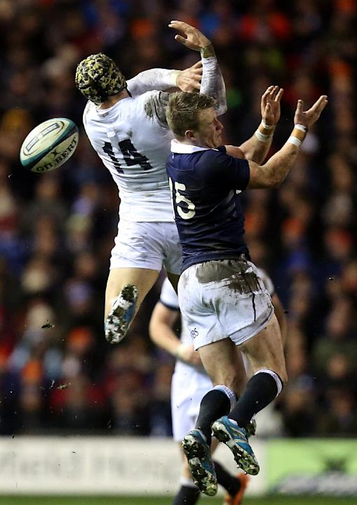 England's Jack Nowell, left, is tackled by Scotland's Stuart Hogg, right, during their Six Nations rugby union international match at Murrayfield, Edinburgh, Scotland, Saturday Feb. 8, 2014