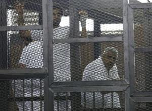 Mohamed Fahmy stands behind bars as he waits to listen the ruling at a court in Cairo