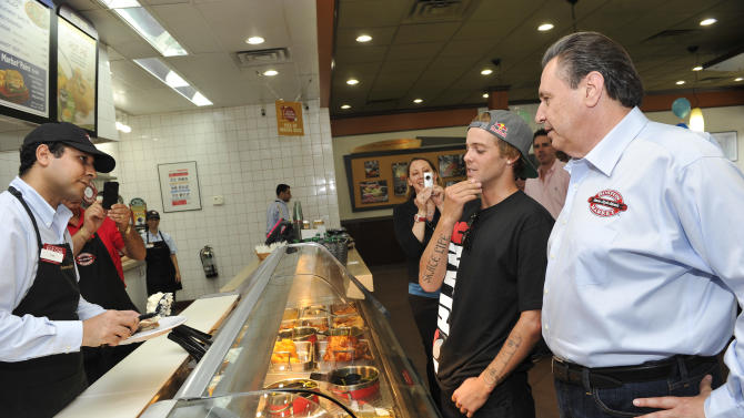 COMMERCIAL IMAGE - Boston Market CEO George Michel (A.K.A. The Big Chicken) and pro skateboarder Ryan Sheckler order lunch at Boston Market during an event benefiting The Sheckler Foundation on Thursday, Aug. 23, 2012 in North Arlington, N.J. (Photo by Charles Sykes/Invision for Boston Market/AP Images)