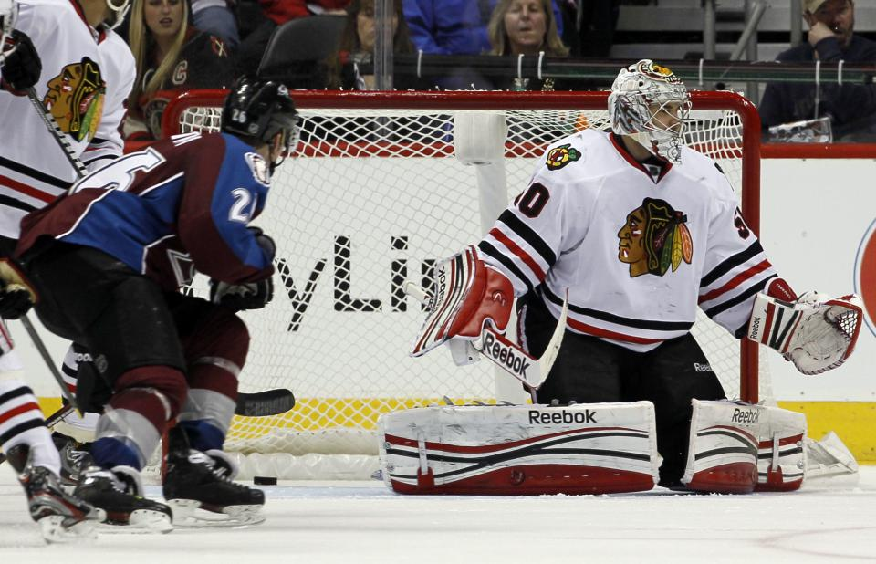 Chicago Blackhawks goalie Corey Crawford, right, reacts after letting in a goal by Colorado Avalanche center Ryan O'Reilly (not shown) as Avalanche center Paul Stastny, left, checks the net in the second period of an NHL hockey game in Denver, Friday, March 8, 2013. (AP Photo/David Zalubowski)