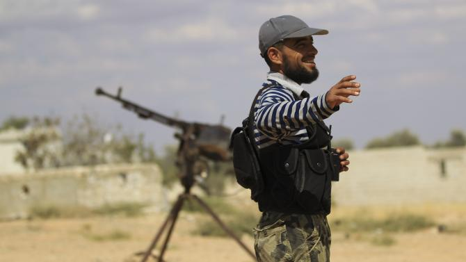 Free Syrian Army fighter gestures beside a machine gun on one of the front lines of Wadi Al-Daif camp in the southern Idlib countryside