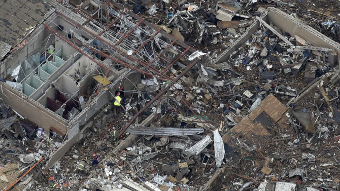 An aerial view shows Plaza Towers Elementary School in Moore, Okla., Tuesday, May 21, 2013 as rescue workers make their way through the structure. At least 24 people, including nine children, were killed in the massive tornado that flattened homes and a school in Moore, on Monday afternoon. (AP Photo/Tony Gutierrez)