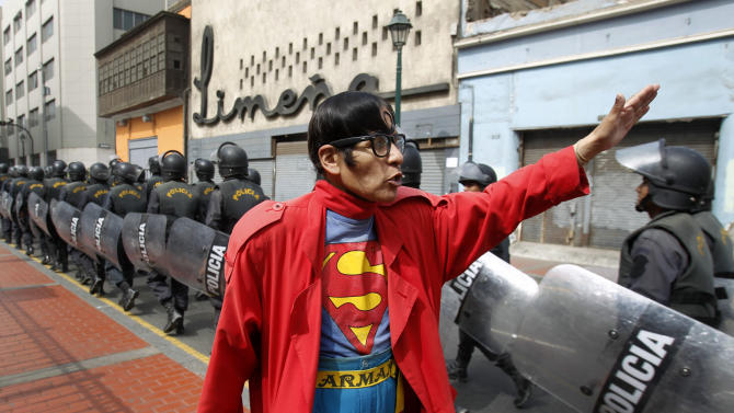 In this photo taken June 13, 2012, Avelino Chavez, wearing his signature Superman costume, waves and greets riot police walking in formation toward a plaza where a protest is expected to take place in downtown Lima, Peru. Chavez, 52, took on the Superman persona 15 years ago, when he lost his job as a security guard, and says he has had work ever since. Chavez also says he only earns about $160 US dollars per month, but that he has the strength of a superhero. Chavez currently works to promote a travel agency. (AP Photo/Martin Mejia)