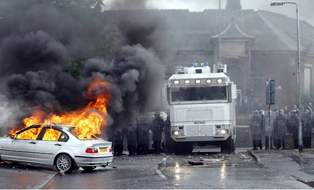 A car burns after Nationalist rioters clashed with Police Service of Ireland in the Ardoyne area of North Belfast, Northen Ireland, Thursday, July 12, 2012.  Trouble broke out after an Orange Order ma
