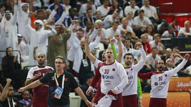 Qatar's coach Riviera and his players on the bench celebrate a goal against France during their final match of the 24th Men's Handball World Championship in Doha